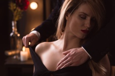 Man gently undressing a woman