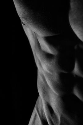 Low key photo of an athletic man with perfect abs