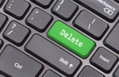 "Computer keyboard closeup with ""Delete"" text on green enter key"