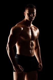 Shirtless muscular guy looking at camera
