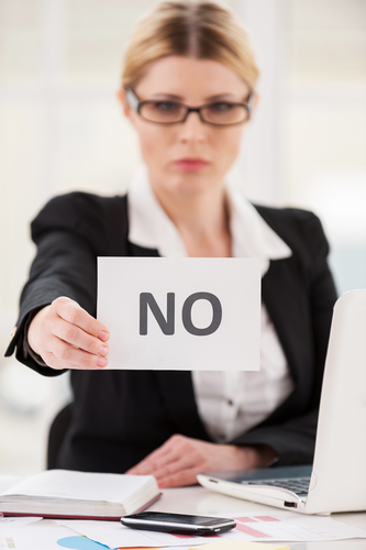 Rejection. Serious mature woman in formalwear saying no to you while stretching out a paper