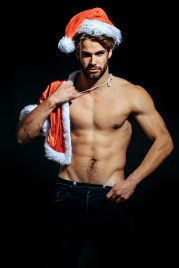 young handsome bearded sexy macho christmas man with long beard in red santa claus hat and coat with muscular bare torso in xmas holiday for new year celebration on black background